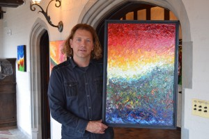 William Butler, poses with one of his many beautiful paintings from his gallery in the Rollins Mansion in Des Moines, Iowa.