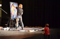 William Butler paints his canvas as a young fan looks on (at the Downtown Church in Des Moines, IA).