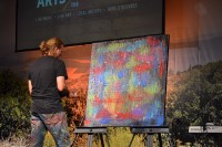 William Butler paints his canvas by hand at the Downtown Church in Des Moines, Iowa.