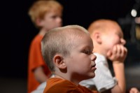 Three young boys look on as William Butler paints at the Downtown Church in Des Moines, Iowa.