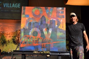 """William Butler, artist from Camden, NJ, poses with his """"Love God. Love All."""" painting he crafted at The Downtown Church in Des Moines, Iowa."""